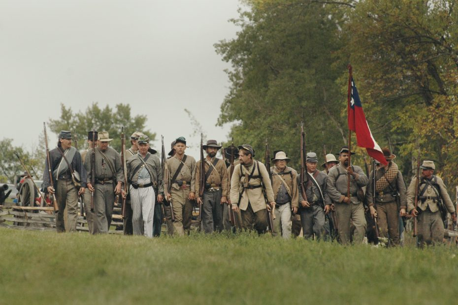 group of men holding hunting gun and flag