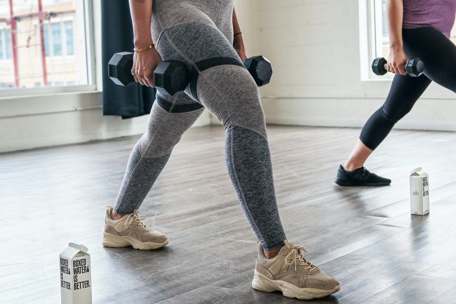 woman in gray sports bra and gray leggings doing push up